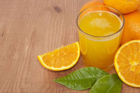 glass of orange juice, oranges and greens photo