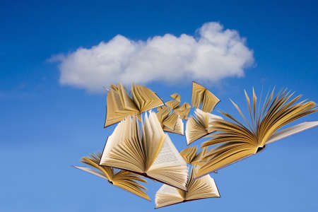 books flying over blue sky with clouds photo
