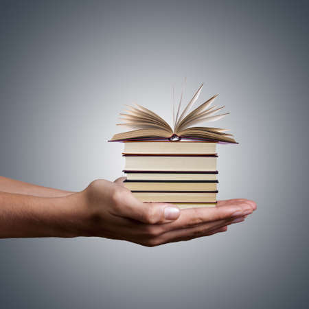hands holding stacked books on white background