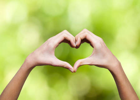 clasped hands forming a heart with natural background