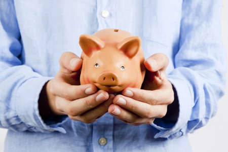 wages: businessman holding piggy bank savings Stock Photo