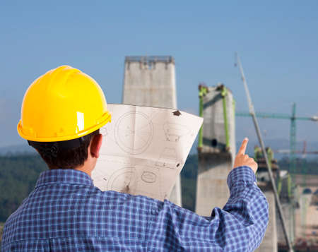 site manager with building plans and background photo