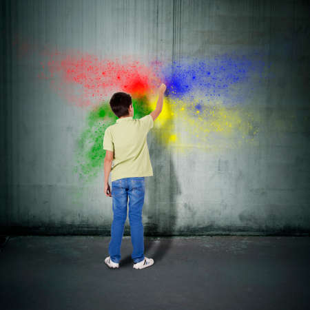 boy painting on the wall with colors photo