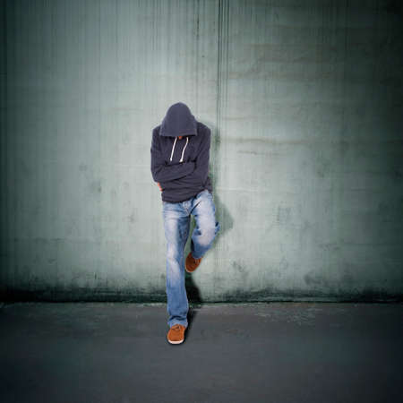young guy leaning against the wall photo