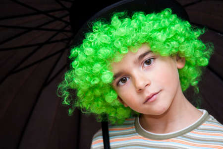 medium body: Portrait of boy with umbrella green wig and looking at camera