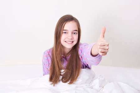 Smiling girl in bed waking up and greeting photo