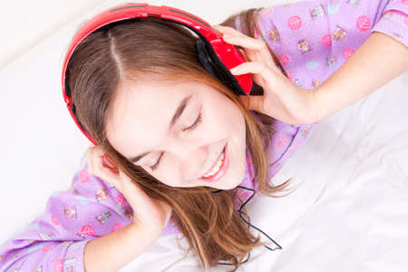 Happy smiling girl with headphones listening to music Stock Photo - 25060268