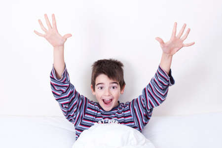 Smiling boy in bed waking up and greeting photo