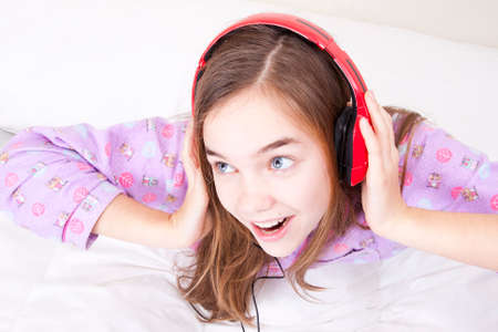 Happy smiling girl with headphones listening to music Stock Photo - 25060288