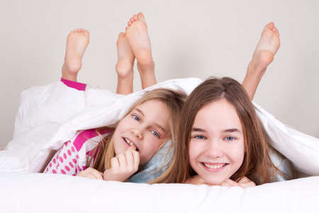 couple smiling girls between the bedclothes photo