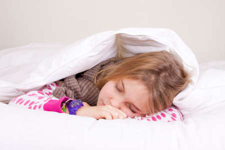 little girl sleeping peacefully in bed covered photo