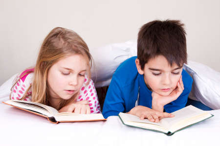 couple of kids in bed covered with blanket reading photo