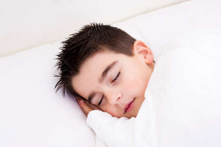 peacefully: Little boy in bed covered with blanket sleeping