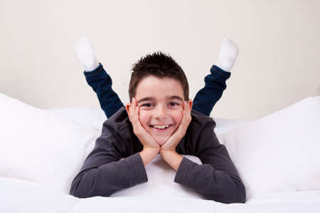 cute little boy with happy expressions in bed photo