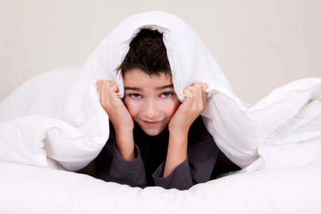 cute little boy with worried expressions in bed photo
