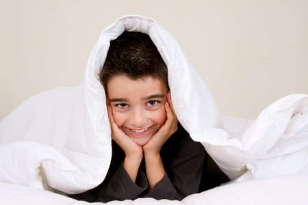 cute little boy with happy expression in bed Stock Photo - 25563180