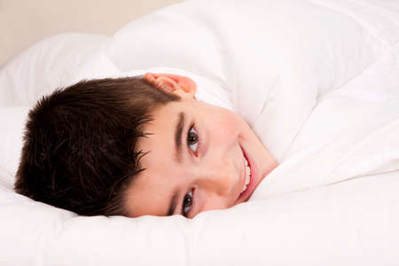 Little boy in bed covered with blanket smiling photo