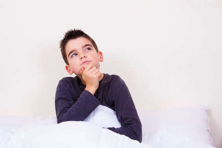 cute little boy with expressions in bed photo