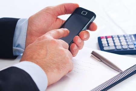 Homme d'affaires travaillant dans le bureau avec un téléphone mobile Banque d'images