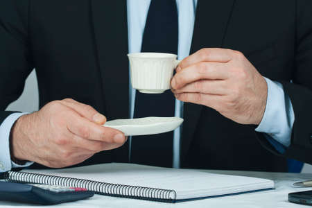 coffee hour: Foreground lifestyle businessman in suit and tie Stock Photo