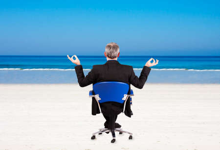 rentals: businessman rentals sand beach with office chair Stock Photo