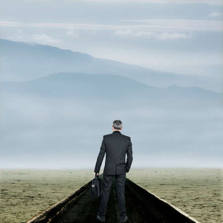 competitiveness: Businessman at the beginning of the road in the desert Stock Photo