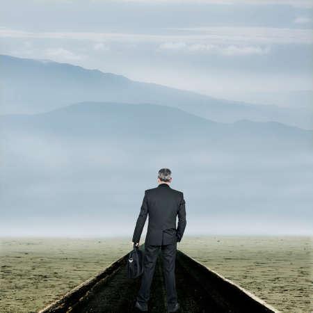 competitividad: Hombre de negocios en el comienzo de la carretera en el desierto