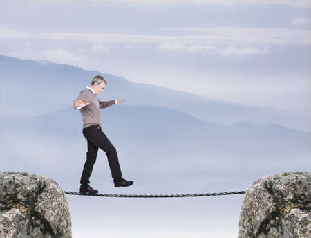 Man balancing on a tightrope in the air photo