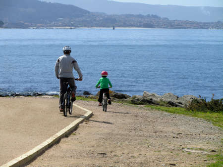 father and son walking bike, familiar scene photo