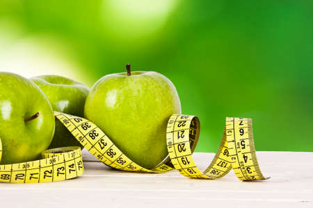 diet healthy: green apples with tape measure, concept of healthy diet