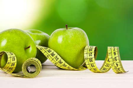 diet healthy: manzanas verdes con cinta m�trica, el concepto de dieta saludable