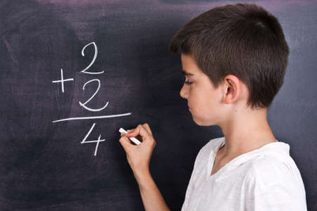child in school blackboard with mathematical formula photo