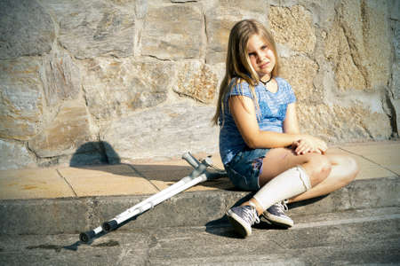 lame: little girl with crutches isolated on white background