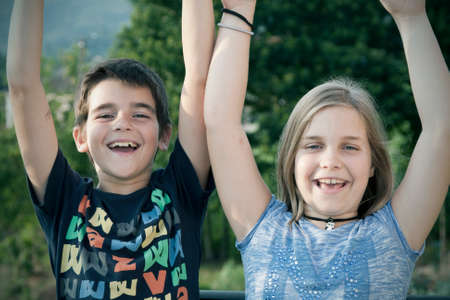 fair complexion: portrait of girl and boy with arms raised in joy. Stock Photo