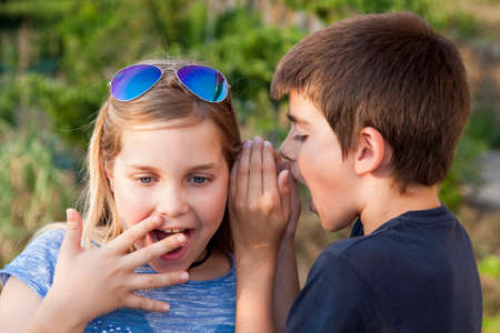 endearing: boy and girl counting a secret to the ear Stock Photo