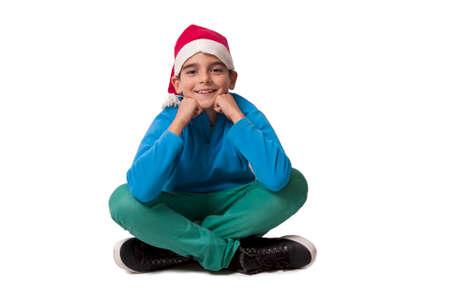 child sitting: child with christmas hat sitting Stock Photo