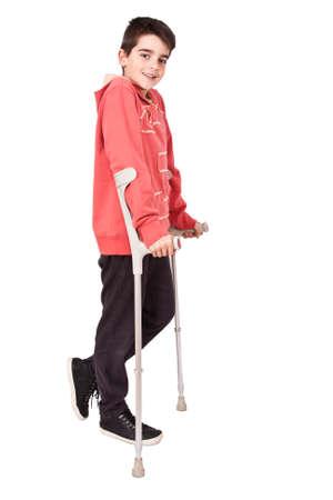 ortopedia: longitud niño con muletas en el fondo blanco Foto de archivo