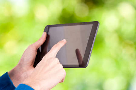 hands with tablet on natural background