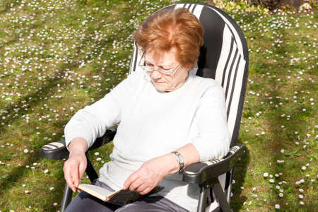third age: cenior woman reading outdoors