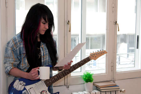 girl playing guitar: Girl playing guitar indoors, lifestyle Stock Photo