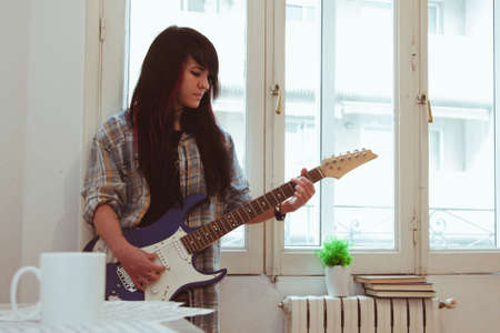 funk music: Girl playing guitar indoors, lifestyle Stock Photo