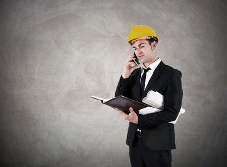 construction safety: architect with plans and helmet work