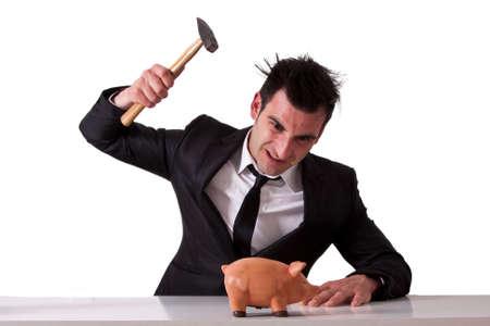 breaking: Business man breaking piggy bank