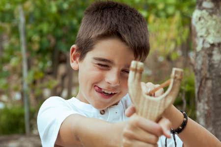 muchacho con la catapulta al aire libre