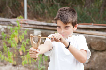 violent: boy with slingshot outdoors Stock Photo