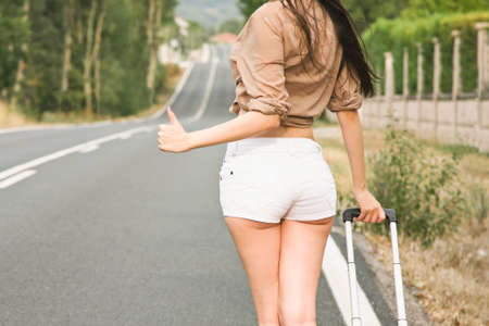 hitchhiking: girl hitchhiking on the road