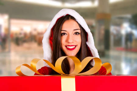santa claus girl with gift box in a shopping center