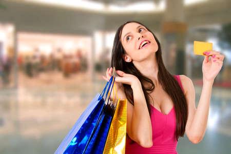 compras compulsivas: mujer con bolsas de compras en centro comercial Foto de archivo