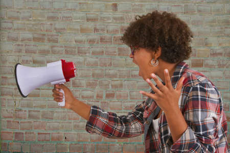 exalted: girl screaming on the megaphone on wall background