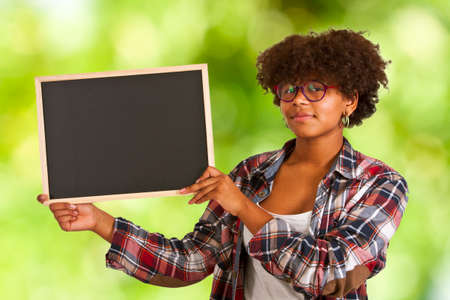 exemplary: colored girl with blackboard on background Stock Photo